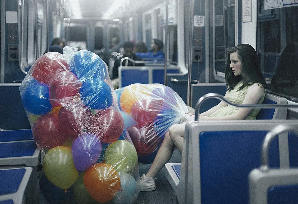 Eine Frau mit vielen Luftballons in der Straßenbahn.