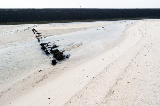 Am Horizont ein Deich, auf dem eine Person läuft, davor Strand und Wasser.