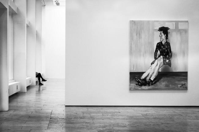 Ein Bild mit einer sitzenden Person im Museum, im Hintergrund sind die Beine eines sitzenden Besuchers zu sehen.