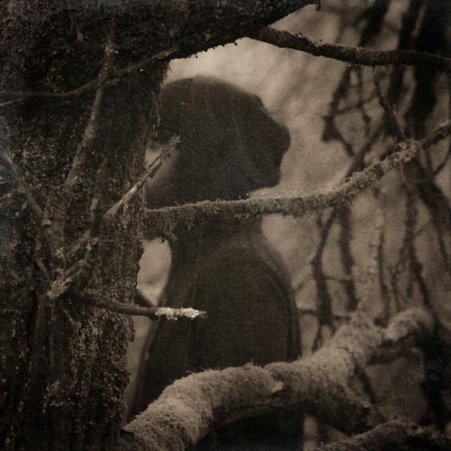 Eine Person hinter einem Baum