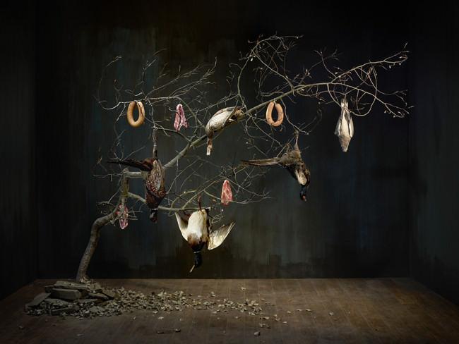 An einem Baum hängen Wurst und Enten.