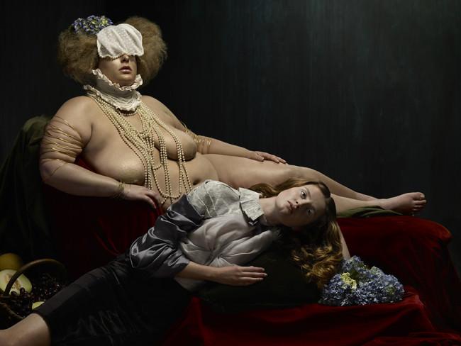 Eine fülligere Frau liegt und berührt mit einer Hand ein Mädchen, das vor ihr liegt.