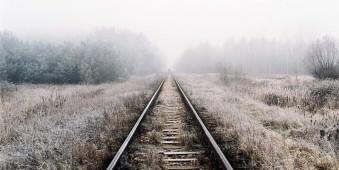 Gleise, die über ein struppiges Feld in den Nebel führen.