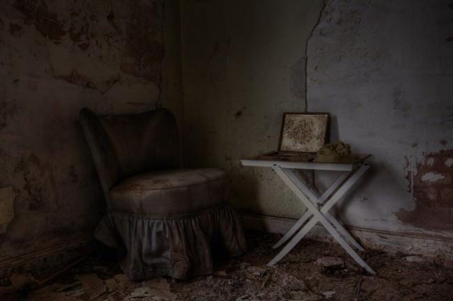 Ein alter Sessel vor einem kleinen Tisch.