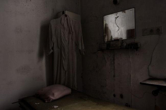 Ein Kleid und ein Spiegel hängen über einer alten Liege.