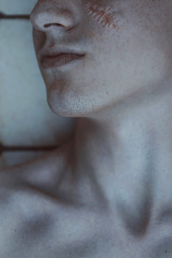 Ausschnitt eines Männergesichts mit Narbe auf der Wange.