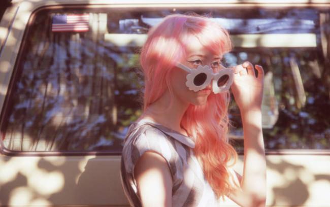 Mädchen mit rosa Haaren und Sonnenbrille in der Sonne.