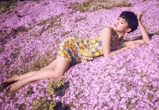 Eine Frau mit Blümchenkleid liegt inmitten von rosa Blumen.