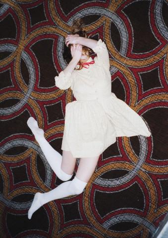 Eine Frau in weißem Kleid springt vor einer 60er Tapete.