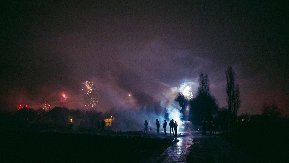 Straße mit Menschen und Feuerwerk.