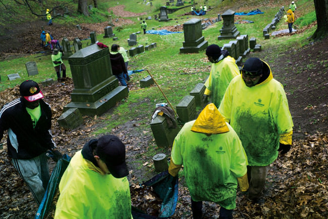 Menschen in grünen Shirts auf einem Friedhof.