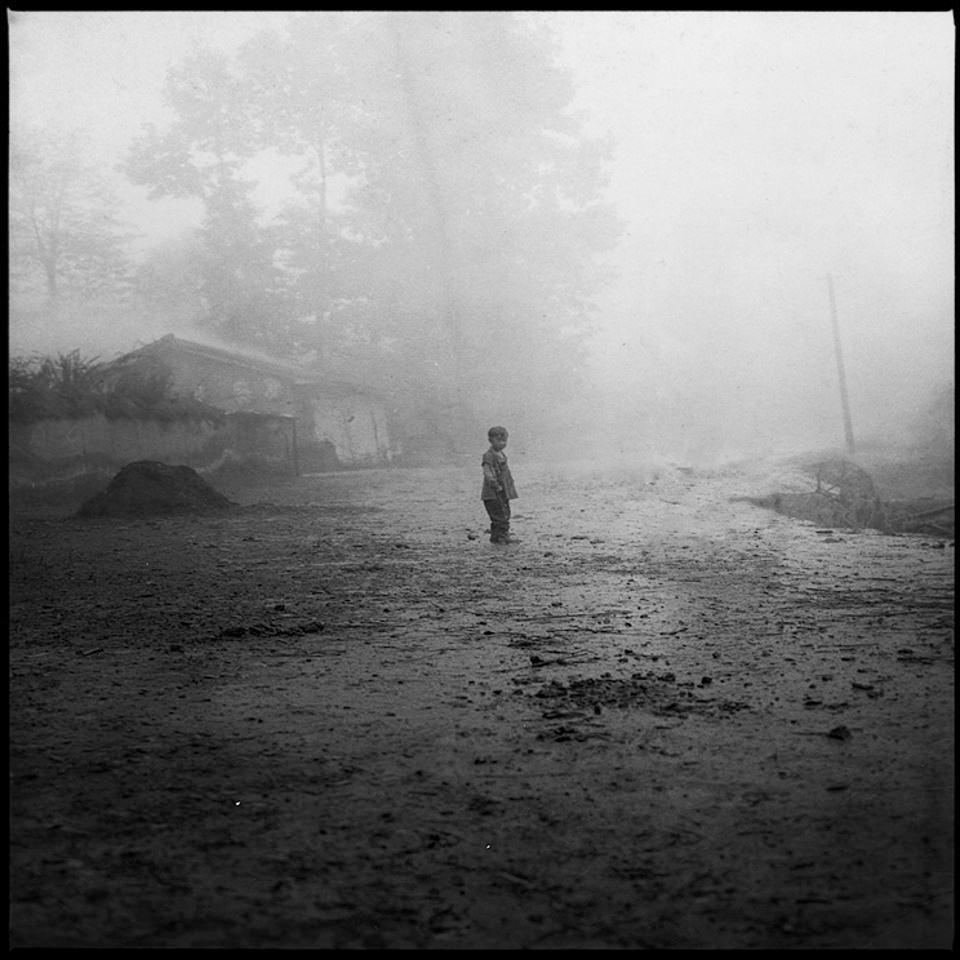 Ein einsames Kind steht auf einem schlammigen Dorfplatz.