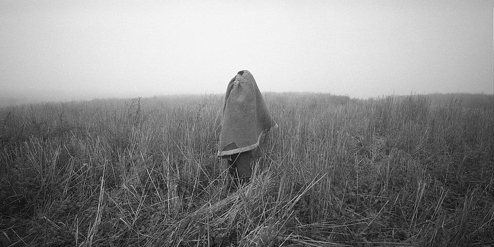 Ein Kind mit einer Decke über dem Kopf steht in einem Feld.