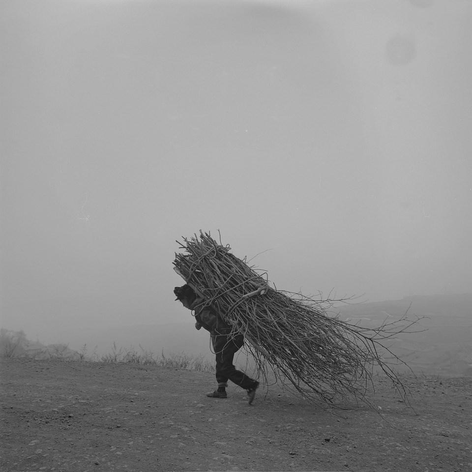 ein Bauer trägt ein riesiges Paket Reisig auf dem Rücken.