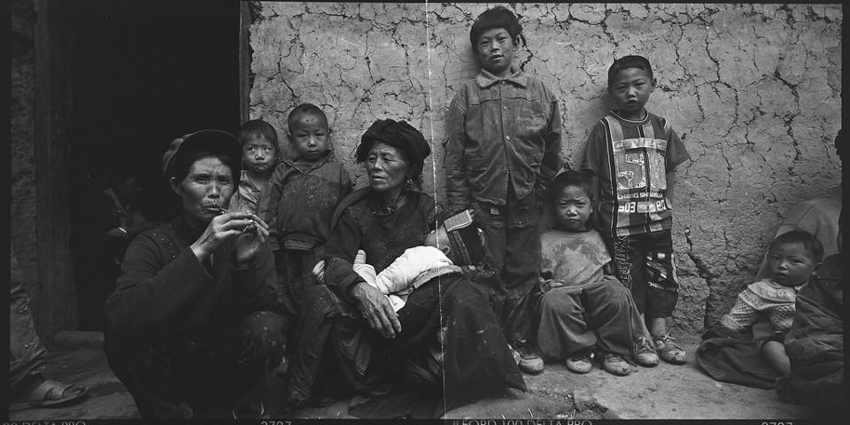 Eine chinesische Yi-Familie sitzt vor ihrer Hütte.