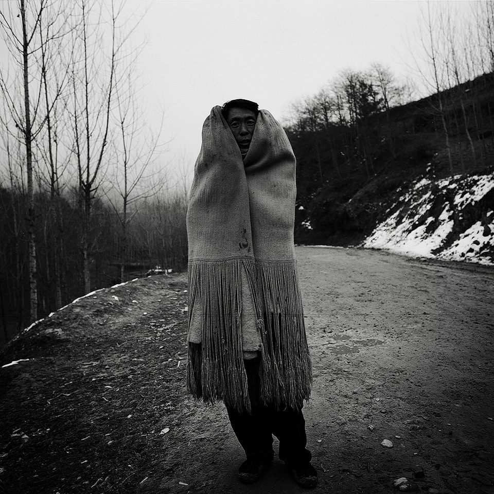 Ein chinesischer Mann hüllt sich in einen Decke.