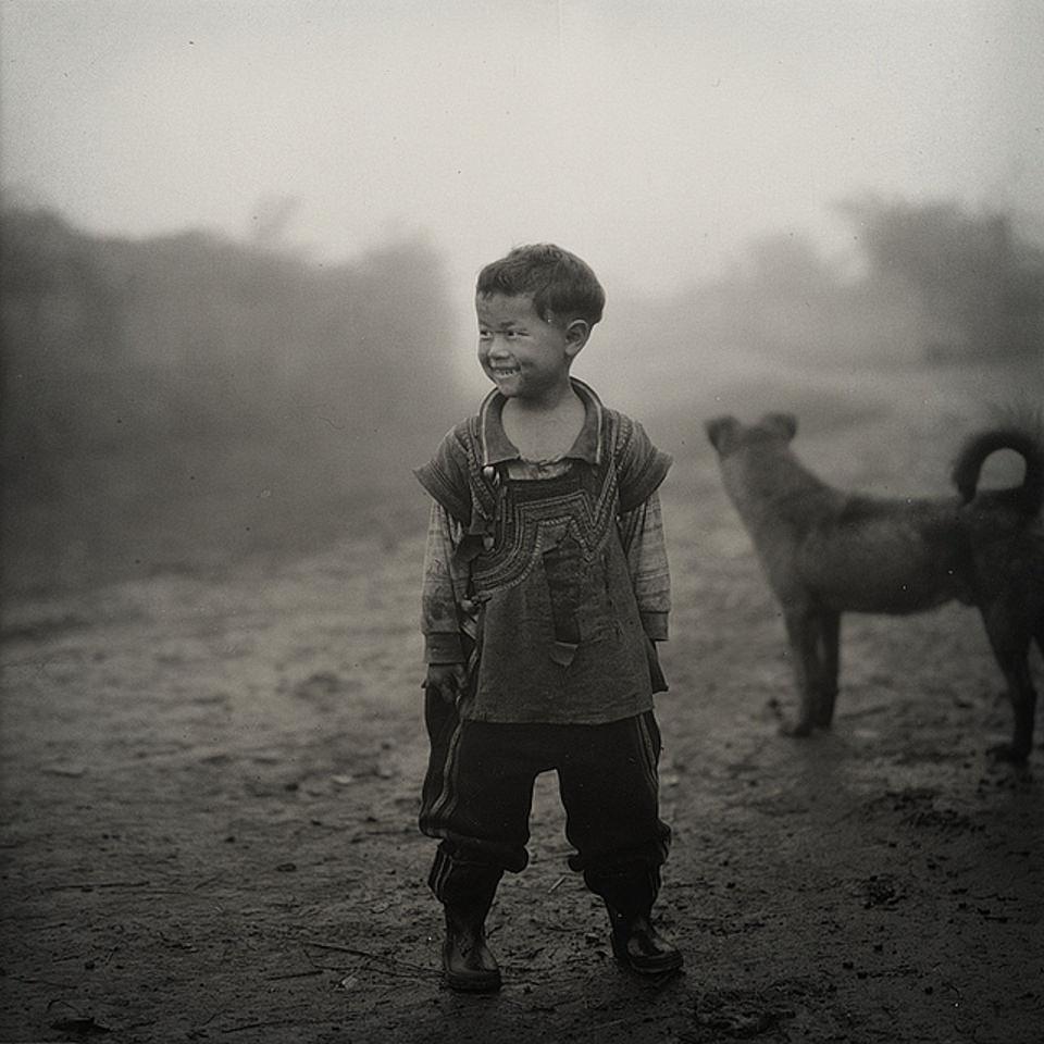 Ein kleiner Junge lacht, hinter ihm steht ein Hund.