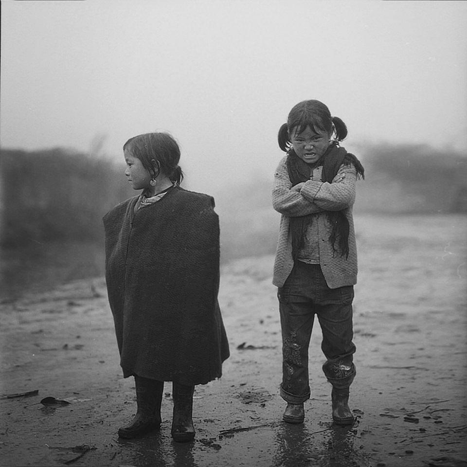 Zwei kleine Mädchen, eines schneidet eine Grimasse.