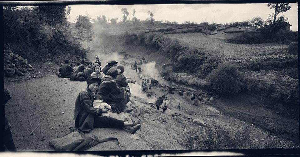 Menschen des Yi-Volkes sitzen zusammen.
