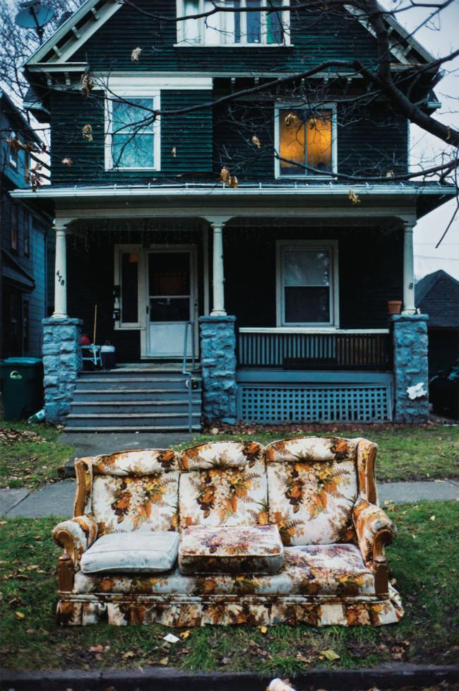 Ein altes Haus und davor ein altes Sofa.