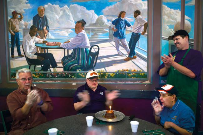 Viele Männer sitzen an einem Tisch und klatschen. Hinter ihnen ein Bild mit Menschen darauf, die ebenfalls an einem Tisch sitzen.