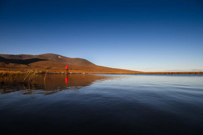 Mann mit roter Jacke an einem See.