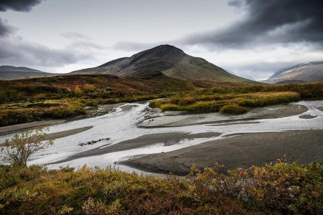 Blick auf ein Flussbett und im Hintergrund ein Berg.