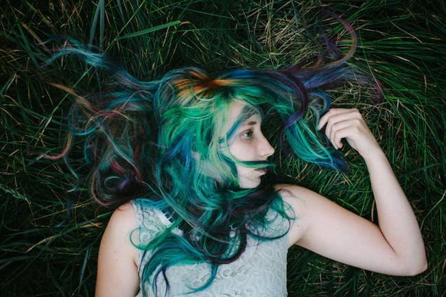 Eine Frau mit bunten Haaren im Gras liegend.