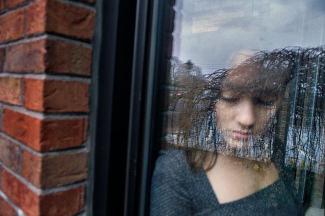 Ein Mädchen steht hinter einer Fensterscheibe und blickt nach unten.