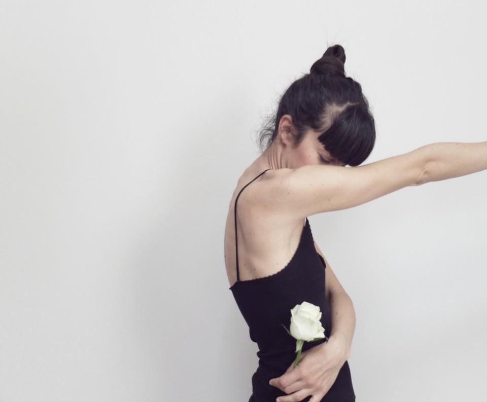 Eine Frau hält in einer Hand eine Blume. Die andere streckt sie weit aus, so das sie durch den Bildrand abgeschnitten ist.
