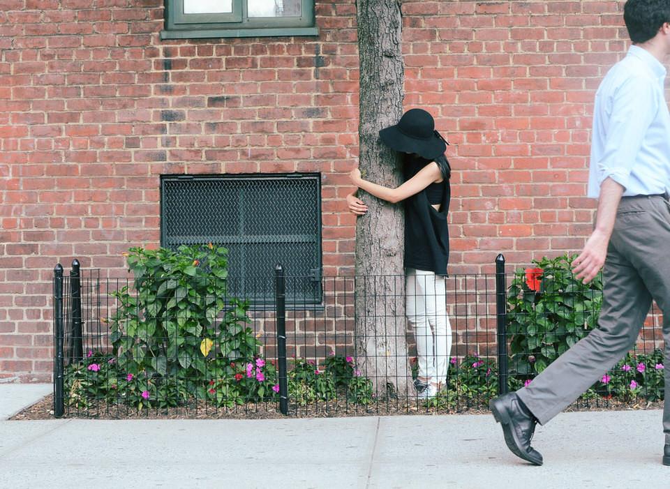 Eine Frau steht in einem eingezäunten kleinen Garten an einer Straße und umarmt einen Baum.