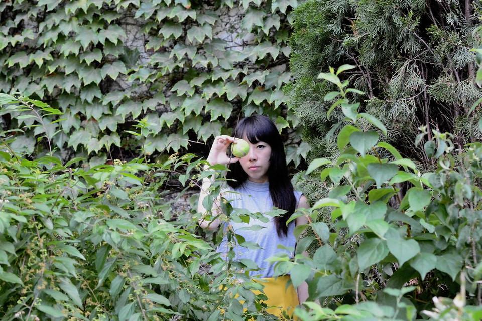 Eine Frau steht im Gebüsch und hält einen Tennisball vor ihr Auge.