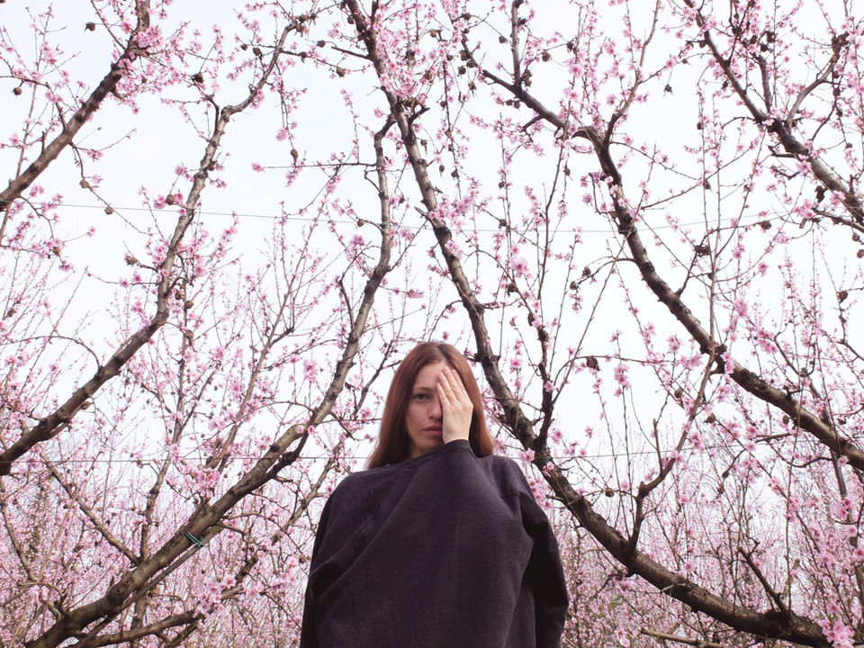 Eine Frau vor einem blühenden Baum hält sich ein Auge zu.