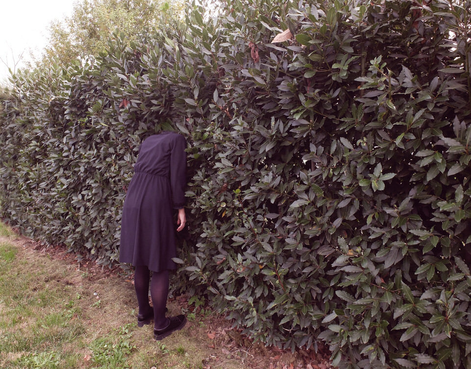 Eine Frau steckt mit dem Kopf in einer Hecke.