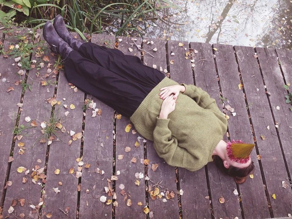 Eine Frau mit Partyhut auf dem Gesicht, liegt auf einem Steg.
