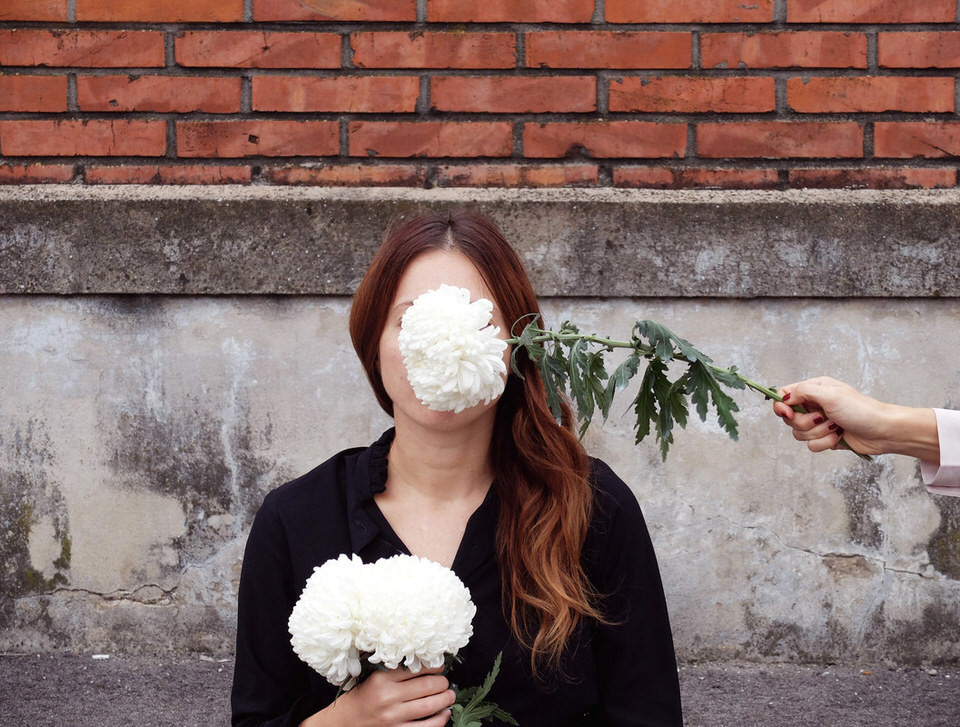 Eine Frau mit weißen Blüten in der Hand und vor dem Gesicht.