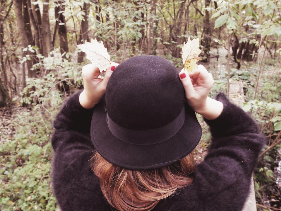 Eine Frau hält zwei Laubblätter wie Hörner an ihren Hut.