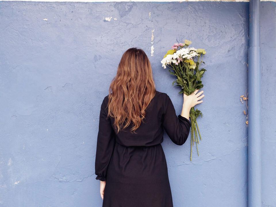 Eine Frau mit Blumenstrauß in der Hand steht an der Wand mit dem Rücken zur Kamera.