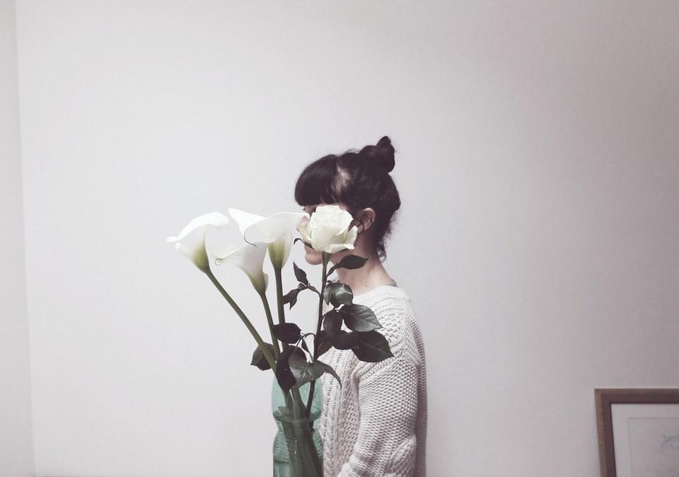 Eine Frau hält einen Strauß aus weißen Blüten vor ihr Gesicht.