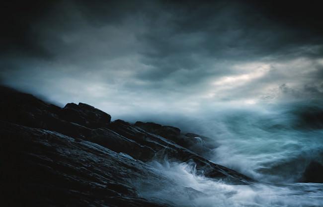 Tosende Wellen treffen auf eine steinerne Küste