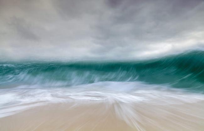 Eine tosende Welle trifft auf den Strand.