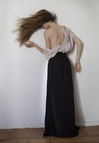 Eine Frau steht an der Wand.
