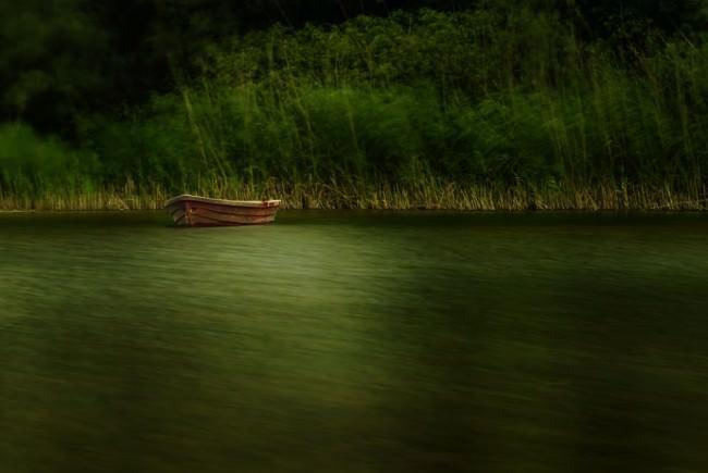 Langzeitbelichtung eines Bootes, das am Ufer eines Sees liegt.