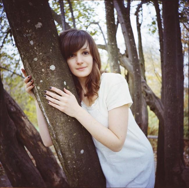 Portrait einer Frau zwischen einigen Bäumen.