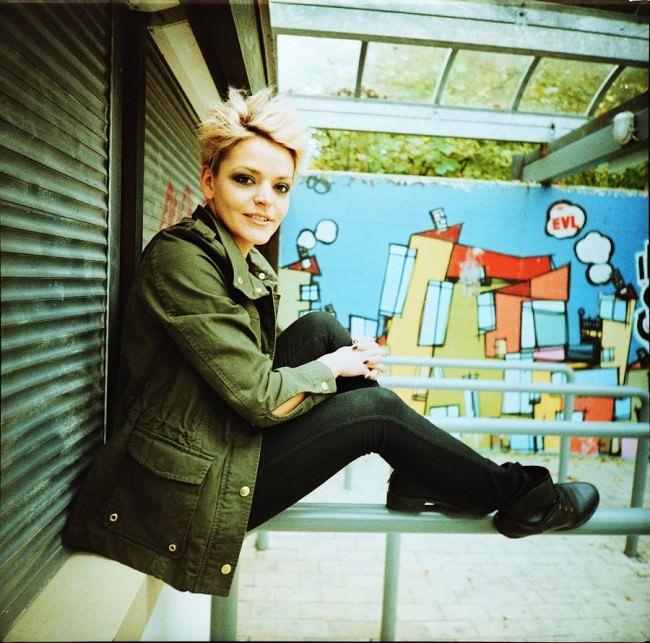 Portrait einer Frau vor einem Graffiti.