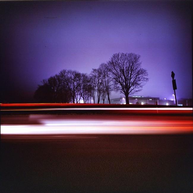 Nächtliche Langzeitbelichtung mit Bäumen und Lichtspuren.