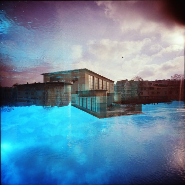Doppelbelichtung mit Gebäuden an einem See und Himmel.