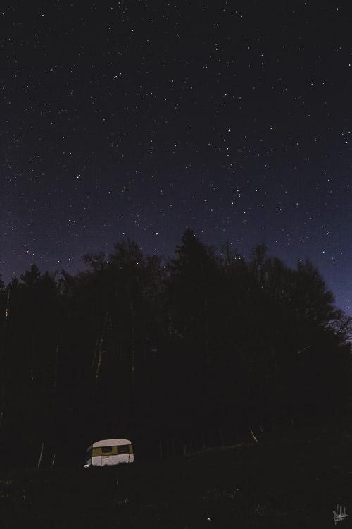 Ein Campingwagen unter dem Sternenhimmel.