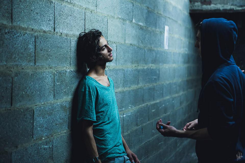 Zwei Männer unterhalten sich, einer lehnt an einer Mauer.