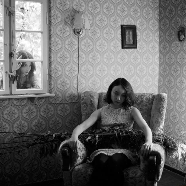 Ein Mädchen sitzt und ein anderes steht draußen vor dem Fenster.